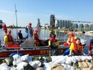 DLRG Bootsbesatzung wartet auf die nächsten Sandsäcke