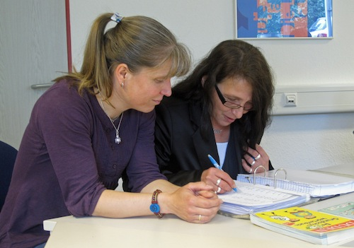 Kursleiterin Sandra Komp und eine Teilnehmerin arbeiten mit Wörterlisten - Bild: OBK
