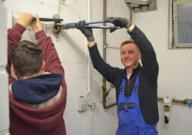 Thomas Meyrahn (Ziess Sanitär- und Heizungstechnik, r.) wird bei der Arbeit von Tagespraktikant Timon. (Foto: OBK)