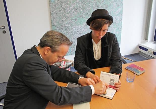 Klaus Grootens stempelt das Reisetagebuch von Tischlergesellin Vannessa Graf. (Foto: OBK)