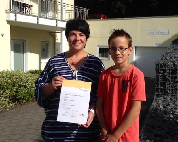 Sabine Valperz und ihr Sohn Jannik freuen sich über das hervorragende 5 Sterne Ergebnis ihrer Ferienwohnung (Quelle: Kurverwaltung Reichshof )