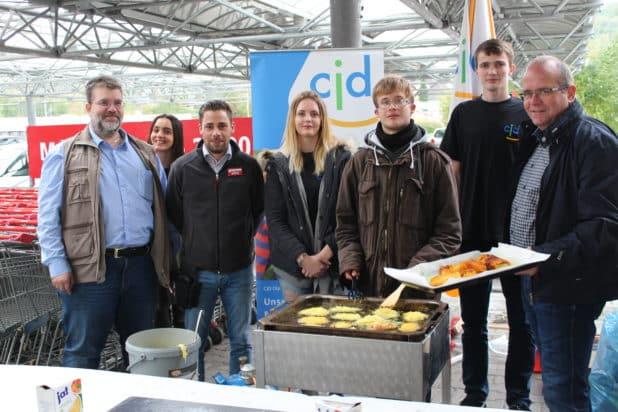 Foto: CJD Ausbilder Stefan Borner (links), REWE Marktleiter Kai Knappe (3. v.l.), CJD Einrichtungsleiter Markus Bröcher (rechts) zusammen mit den Jugendlichen bei der Reibekuchenzubereitung.